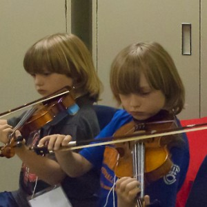 twin boys playing fiddle